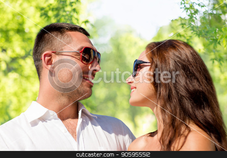 happy couple in sunglasses over green background stock photo, love, summer and relationships concept - happy smiling couple in sunglasses over green natural background by Syda Productions