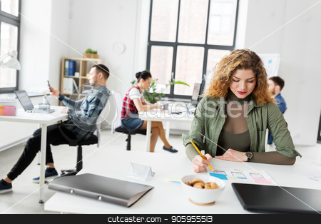 creative woman working on user interface at office stock photo, business, technology and people concept - creative woman or developer working on user interface design at office by Syda Productions