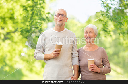 senior couple with coffee cups natural background stock photo, old age and people concept - happy senior couple with coffee cups over green natural background by Syda Productions