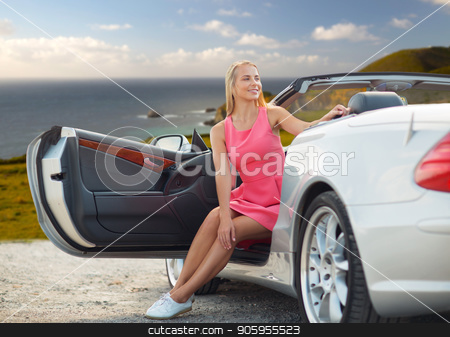 woman posing in convertible car over big sur coast stock photo, travel, road trip and people concept - happy young woman posing in convertible car over big sur coast of california background by Syda Productions
