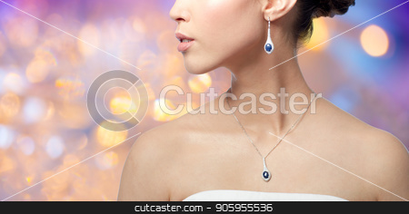close up of woman with earring and pendant stock photo, beauty, jewelry, people and luxury concept - close up of beautiful asian woman or bride with earring and pendant over holidays lights background by Syda Productions