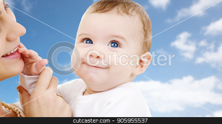 mother with baby over sky background stock photo, family and motherhood concept - happy smiling young mother with little baby over sky background by Syda Productions