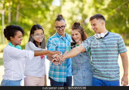happy friends stacking hands in park stock photo, unity, friendship and international concept - group of happy smiling friends stacking hands in park by Syda Productions