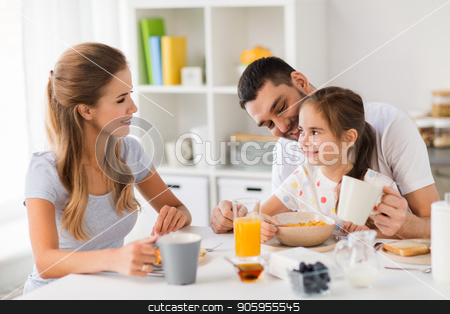 happy family having breakfast at home stock photo, family, eating and people concept - happy mother, father and daughter having breakfast at home by Syda Productions