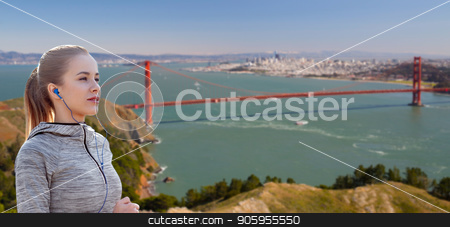 woman with earphones running over san francisco stock photo, fitness, sport and technology concept - happy woman running and listening to music in earphones over golden gate bridge in san francisco bay background by Syda Productions
