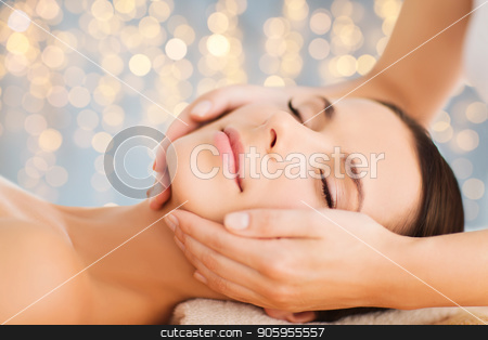 close up of beautiful woman having face massage stock photo, wellness, spa and beauty concept - close up of beautiful woman having face massage over holidays lights background by Syda Productions
