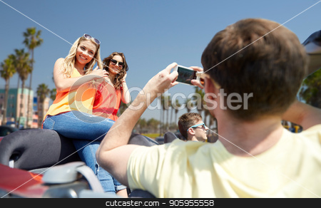 friends photographing in car over venice beach stock photo, leisure, road trip, travel and people concept - happy friends taking picture by smartphone in convertible car over venice beach background in california by Syda Productions