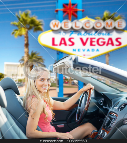 happy woman driving convertible car at las vegas stock photo, travel, road trip and people concept - happy young woman driving convertible car over welcome to fabulous las vegas sign background by Syda Productions