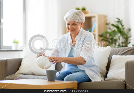 senior woman drinking tea at home stock photo, age, drink and people concept - senior woman pouring tea from teapot to cup and drinking it at home by Syda Productions