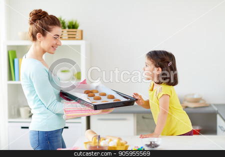 happy mother and daughter baking cookies at home stock photo, family, cooking and people concept - happy mother holding tray of cookies and little daughter at home kitchen by Syda Productions
