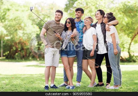 friends taking picture by selfie stick at summer stock photo, friendship, leisure and technology concept - group of happy smiling friends taking picture by selfie stick at summer park by Syda Productions