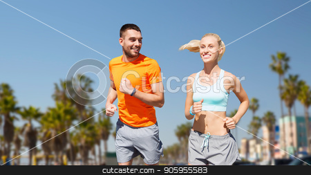 couple running over venice beach background stock photo, fitness, sport and healthy lifestyle concept - smiling couple with heart-rate watch running over venice beach background in california by Syda Productions