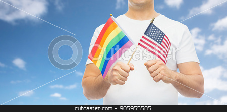 man with gay pride rainbow and american flag stock photo, lgbt, same-sex relationships and homosexual concept - close up of man holding gay pride rainbow and american flag over blue sky and clouds background by Syda Productions