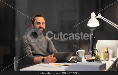 creative man with computer working at night office stock photo, deadline, technology and people concept - creative man with tablet pc computer working late at night office by Syda Productions