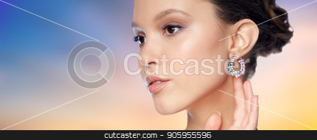 close up of beautiful woman face with earring stock photo, beauty, jewelry, people and luxury concept - close up of beautiful asian woman face with earring over pastel background by Syda Productions