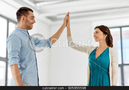 happy couple making high five gesture at new home stock photo, mortgage, people and real estate concept - happy couple at new home making high five gesture by Syda Productions