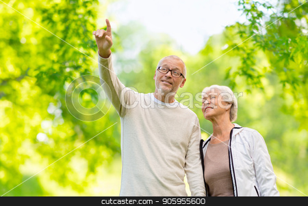 happy senior couple over green natural background stock photo, old age and people concept - happy senior couple over green natural background by Syda Productions