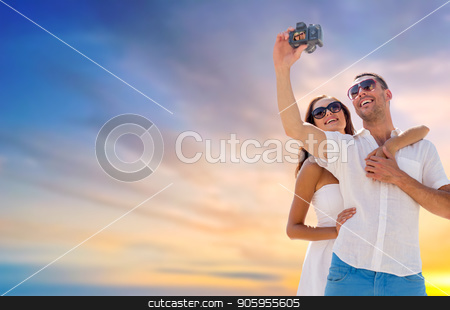 smiling couple making selfie by digital camera stock photo, love, summer and technology concept - smiling couple in sunglasses making selfie by digital camera over evening sky background by Syda Productions