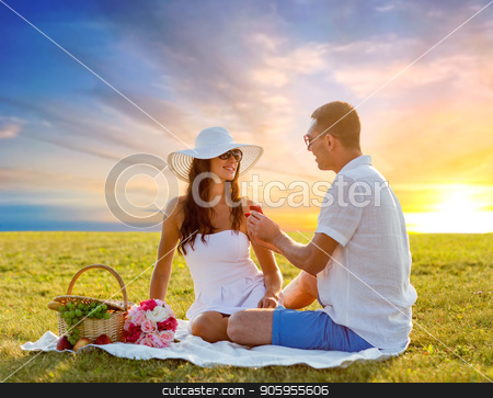 happy couple with small red gift box at picnic stock photo, proposal, engagement and love concept - happy couple with small red gift box at picnic on meadow over sunset sky background by Syda Productions