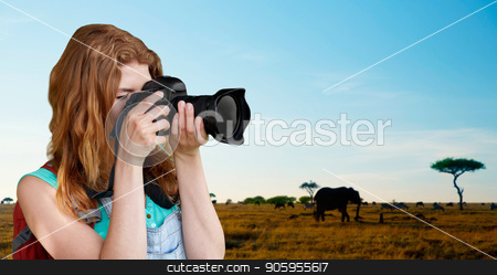 woman with backpack and camera over savannah stock photo, travel, tourism and photography concept - happy young woman with backpack and camera photographing over animals in african savannah background by Syda Productions