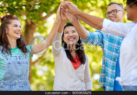 happy friends making high five in park stock photo, success, friendship and international concept - group of happy smiling friends making high five in park by Syda Productions