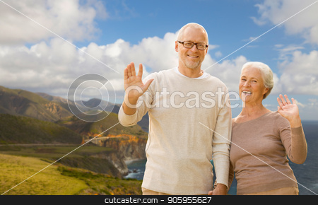 senior couple waving hands over big sur coast stock photo, old age, tourism, travel and people concept - happy senior couple waving hands over bixby creek bridge on big sur coast of california background by Syda Productions