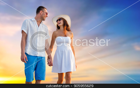 happy couple on vacation walking holding hands stock photo, love, summer and relationships concept - happy couple on vacation wearing sunglasses and walking holding hands over evening sky background by Syda Productions