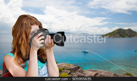 woman with backpack and camera over seychelles  stock photo, travel, tourism and photography concept - happy young woman with backpack and camera photographing over background of seychelles island in indian ocean by Syda Productions