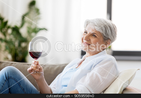 happy senior woman with glass of red wine at home stock photo, people, alcohol and leisure concept - happy smiling senior woman with glass of red wine at home by Syda Productions