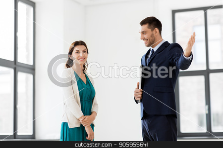 realtor showing new office room to female customer stock photo, real estate business, sale and people concept - happy smiling realtor with folder showing new office room to female customer by Syda Productions