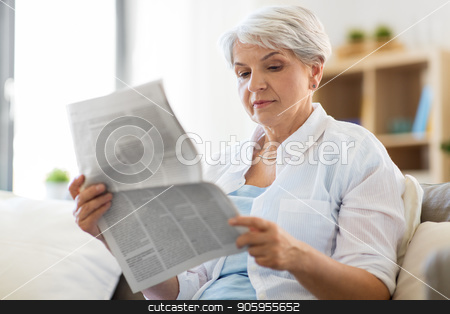 senior woman reading newspaper at home stock photo, age and people concept - senior woman reading newspaper at home by Syda Productions