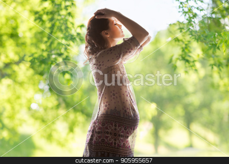 pregnant woman over green natural background stock photo, pregnancy, motherhood, people and expectation concept - pregnant woman posing over green natural background by Syda Productions