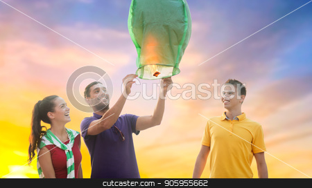 happy friends lighting chinese sky lantern stock photo, celebration and people concept - group happy friends lighting chinese sky lantern outdoors by Syda Productions