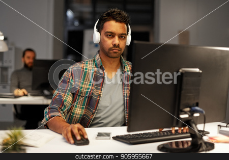 creative man with headphones working at office stock photo, deadline, technology and people concept - creative man with headphones and computer listening to music and working at night office by Syda Productions