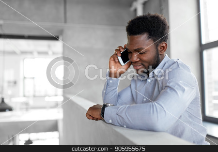 businessman calling on smartphone at office stock photo, business, technology, communication and people concept - african american businessman calling on smartphone at office by Syda Productions
