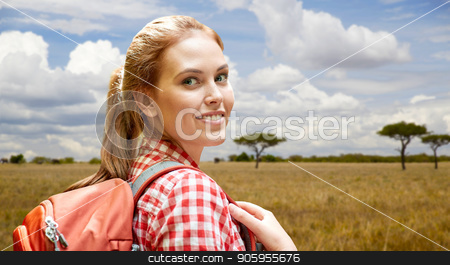 happy woman with backpack over african savannah stock photo, adventure, travel, tourism, hike and people concept - smiling young woman with backpack over african savannah background by Syda Productions