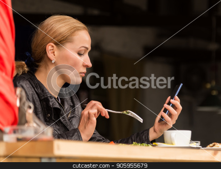businesswoman eating salad in an outdoor cafe. Healthy lifestyle: girl eating green tasty food and checks email on your phone stock photo, businesswoman eating salad in an outdoor cafe. Healthy lifestyle: girl eating green tasty food by Alexander