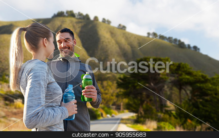 couple of sportsmen with water over big sur hills stock photo, fitness, sport and people concept - smiling couple with bottles of water over big sur hills background in california by Syda Productions