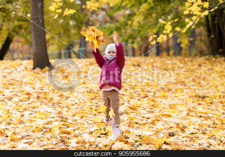happy girl playing with leaves at autumn park stock photo, childhood, season and people concept - happy little girl playing with fallen leaves at autumn park by Syda Productions