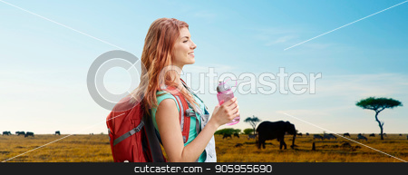 happy woman with backpack over african savannah stock photo, adventure, travel, tourism, hike and people concept - smiling young woman with backpack and bottle of water over animals in african savannah background by Syda Productions
