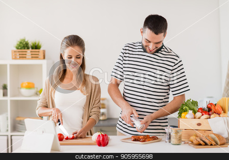 happy couple cooking food at home kitchen stock photo, people and healthy eating concept - happy couple cooking food at home kitchen by Syda Productions
