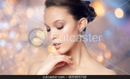 close up of beautiful woman face with earring stock photo, beauty, jewelry, accessories, people and luxury concept - close up of beautiful asian woman face with earring over gray background by Syda Productions