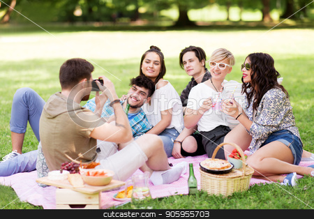 friends photographing at picnic in summer park stock photo, friendship, leisure and technology concept - group of happy smiling friends with non alcoholic drinks photographing at picnic in summer park by Syda Productions