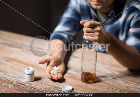 unhappy drunk man with bottle of alcohol and pills stock photo, depression, drug abuse and addiction people concept - unhappy drunk man with bottle of alcohol and pills committing suicide by overdosing on medication at night by Syda Productions
