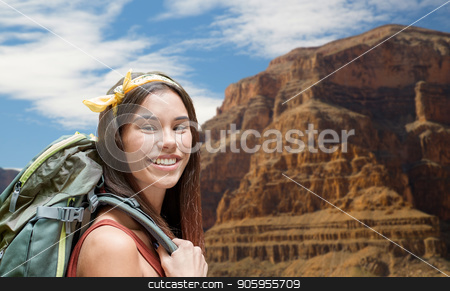 happy woman with backpack over grand canyon stock photo, adventure, travel, tourism, hike and people concept - smiling young woman with backpack over grand canyon national park background by Syda Productions