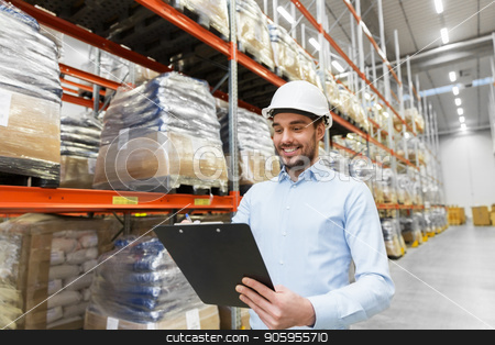 businessman in helmet with clipboard at warehouse stock photo, logistic business, shipment and people concept - businessman in helmet with clipboard checking goods at warehouse by Syda Productions