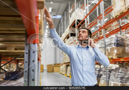 businessman calling on smartphone at warehouse stock photo, wholesale, logistic business, technology and people concept - businessman calling on smartphone at warehouse by Syda Productions