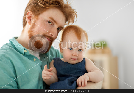 portrait of father with little baby daughter stock photo, family, fatherhood and people concept - portrait of red haired father with little baby daughter at home by Syda Productions