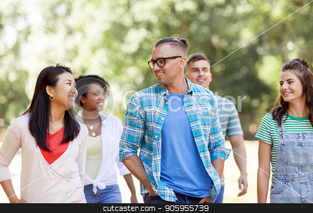 group of happy international friends in park stock photo, people, friendship and international concept - group of happy friends walking in park by Syda Productions