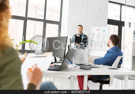 man showing tablet pc to creative team at office stock photo, business, technology and people concept - man showing tablet pc computer to creative team at office presentation by Syda Productions